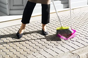 woman sweeping sidewalk