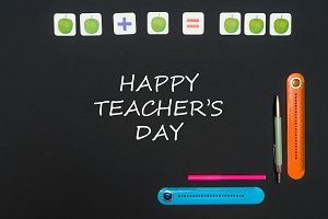 Black art table with stationery supplies with text happy teacher's day on blackboard