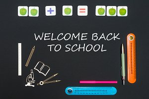 Above stationery supplies and text welcome back to school on blackboard