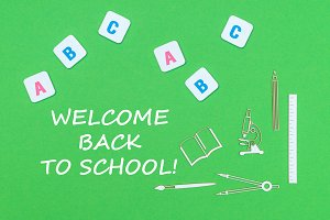 text welcome back to school, from above wooden minitures school supplies and abc letters on green background