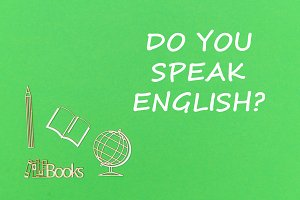 text do you speak english, school supplies wooden miniatures on green background