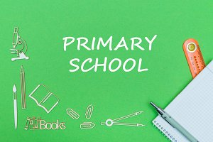 text primary school, school supplies wooden miniatures, notebook with ruler, pen on green backboard