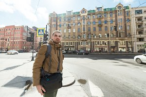 Young hipster man traveling backpacker outdoor in Saint-Petersburg street. He is on crossroads Travel, hiking concept