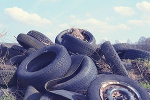 Pile of wasted tires under blue sky