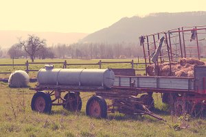 Hay cart and a water tank on a field
