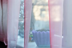 Transparent pink curtain on window