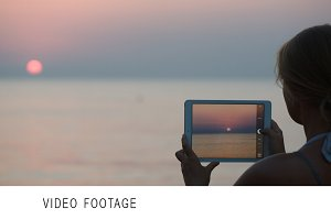 Woman making photo of sunset using