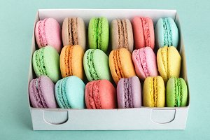 colorful macaroons in box on green white background closeup