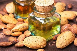 Almond oil in bottle and nuts