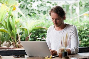 Young male freelancer sitting in cafe working in laptop