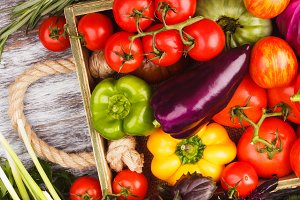 Set of different fresh raw vegetables in the wooden tray, light background