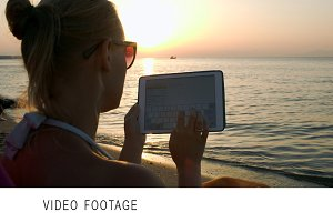Woman typing on pad sitting by sea