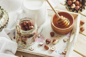 Honey in the wooden bowl, hazelnuts and jar with milk on the wooden tray