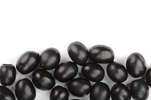 whole black olives isolated on white background with copy space for your text. Top view. Flat lay pattern