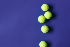 Yellow tennis balls on violet paper