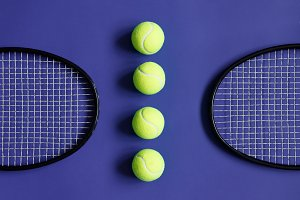 Tennis balls and two black tennis rackets. Violet background. Concept sport, competition, match.
