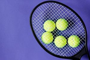 Tennis balls under black racquet