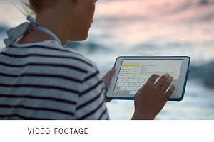 Woman with tablet PC by sea on windy