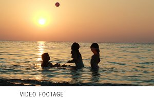 Girls playing with ball sea sunset