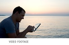 Young man by the sea typing message