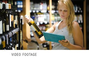 Woman choosing wine using pad