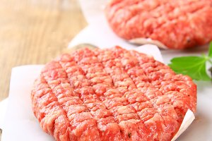 Raw minced meat for home made grill burgers cooking with spaces and herbs.