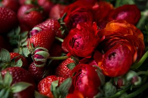 red fresh strawberry lies next to red flowers