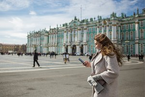 Young traveler woman wearing casual classic coat, holding cellphone, using app, gps, searching for direction while walking in Saint-Petersburg, Palace Square, Winter Palace in spring or autumn time