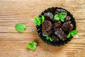 Prunes with mint leaves in a bowl on an old wooden table.