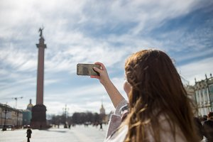 Young traveler woman wearing casual classic coat, holding cellphone and taking photo Alexandrian Column while walking in Saint-Petersburg, Palace Square in spring or autumn time
