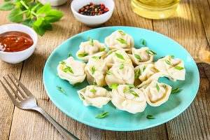 Homemade ready dumplings on an old wooden table.