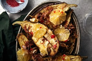 Overhead image of traditional jewish and middle eastern food roasted eggplants with lemon
