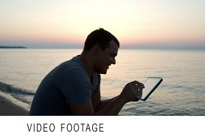 Man using tablet computer on beach