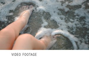 Childs feet washing with sea waves