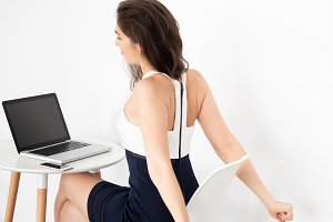Young Caucasian working business woman on desk with laptop stretching some exercises to take a break from work