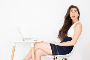 Young beautiful business woman surprised and shocked sitting on desk with laptop