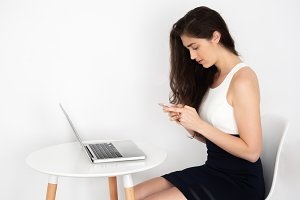 Smart looking young business woman using phone in many online internet activities such as texting, reading,typing