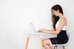 Young attractive Caucasian business woman working and typing on laptop on desk