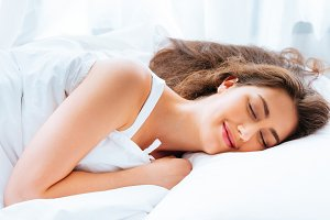 Happy Young Caucasian woman smiling and sleeping in bed with relaxation and tranquil and calm mind in white background