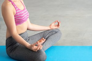 Close up of Young Caucasian woman in yoga sport clothes meditating and doing lotus yoga position in peaceful and calm posture