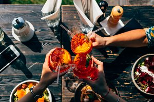 Raising a glasses with aperol spritz