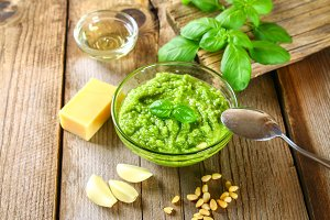 Homemade pesto sauce. Ingredients. Cheese, garlic, basil, pine nuts, olive oil on an old wooden table.