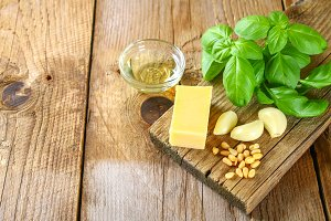 Ingredients for pesto sauce. Cheese, garlic, basil, pine nuts, olive oil.