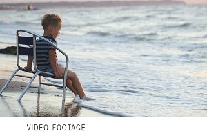 Boy sitting on the chair by sea