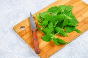 Leaves of fresh green nettle on a cutting wooden board with a knife on a gray concrete table.