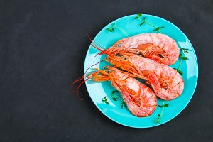 Large royal raw frozen prawns on a blue plate with thyme and basil on a concrete table. Red shrimps. Top view.