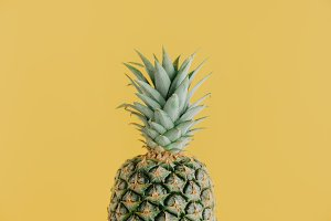 Green pineapple on yellow background