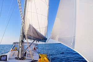 View from a sailboat's bow with mast and full sails