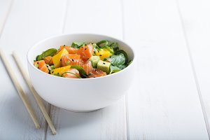 Hawaiian Poke salad with salmon, avocado and vegetables in a bowl on a white wooden rustic background with copy space, vegetables and chopsticks. Horizontal