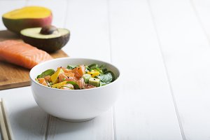 Hawaiian Poke salad with salmon, avocado and vegetables in a bowl on a white wooden rustic background with copy space, vegetables and chopsticks